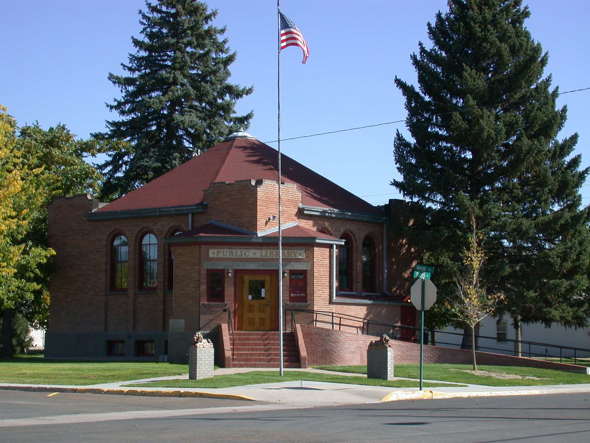 brick building with corner entrance; flag pole flanked by small statues of lions in front