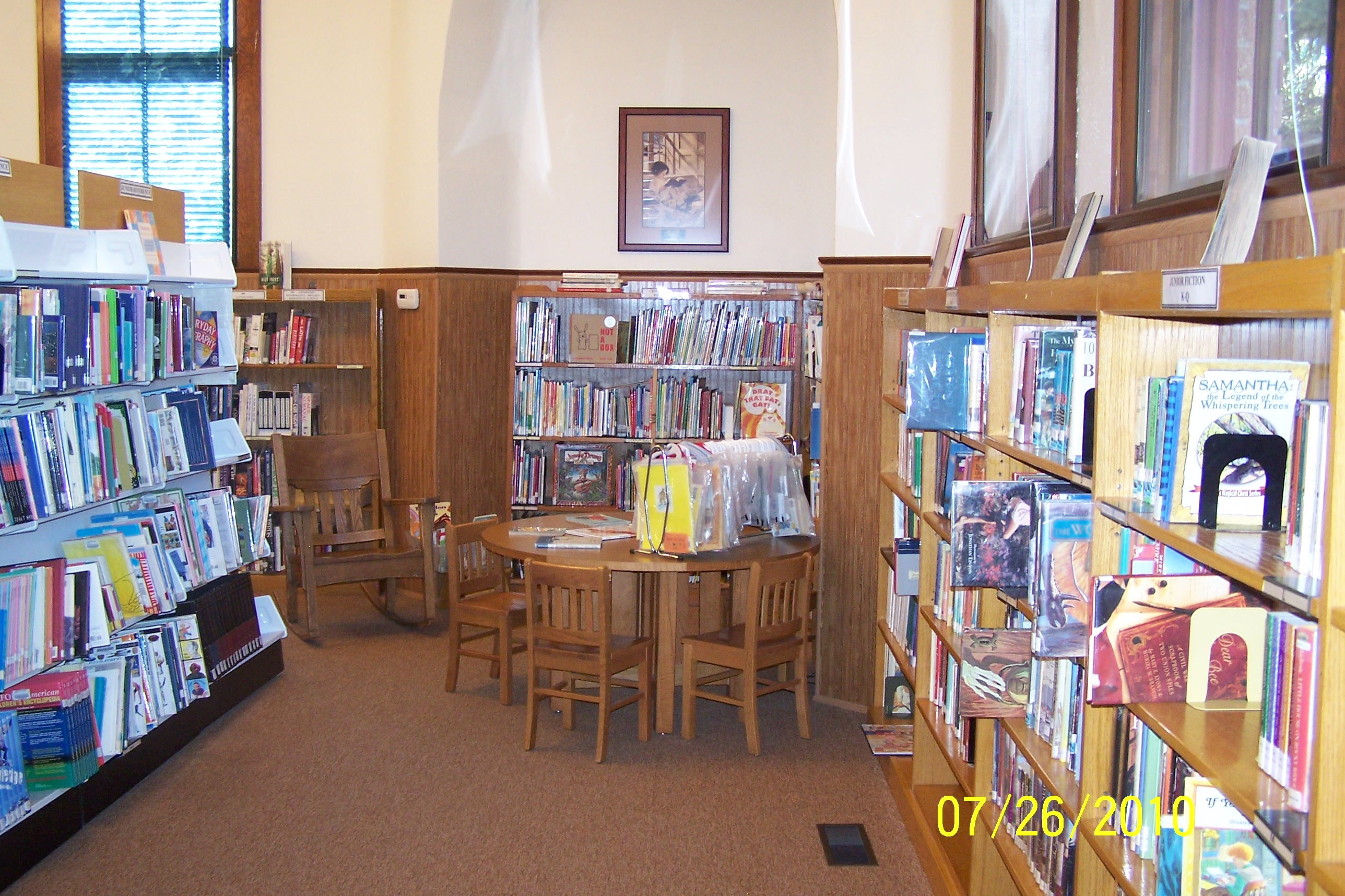 small wood table and chairs surrounded by shelves of children's books
