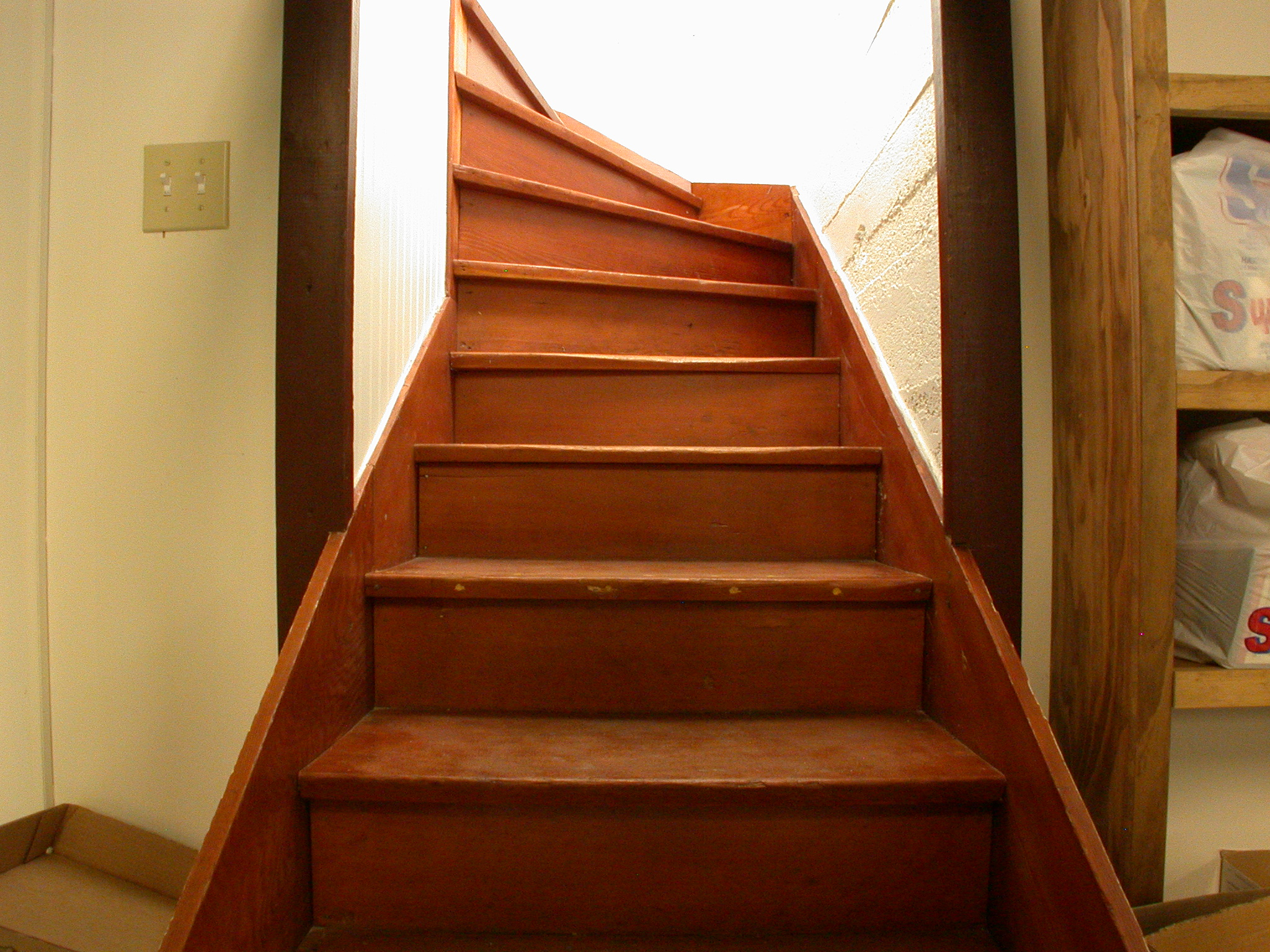 wooden staircase going up and winding to the left